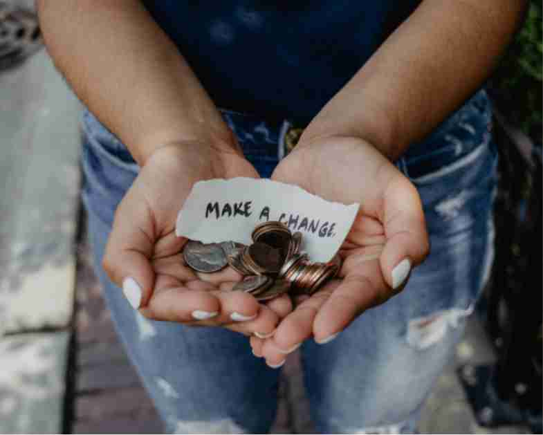 Person holding coins with a note that reads Make a Change